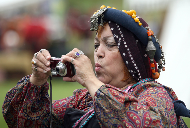 Allurinda of Tacoma who is dressed in a Middle Eastern costume uses a modern digital camera to take photos at the June Faire in Port Gamble on Saturday. LARRY STEAGALL / KITSAP SUN