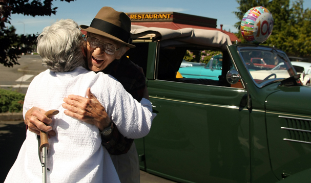 Charline Austin, of Poulsbo, is the first friend to give Bob Bartos a hug for his birthday after he exited his 1936 Ford 4-door convertible sedan at the Cool Car Cruz in the parking lot of Shari's Restaurant on Wheaton Way in Bremerton on Tuesday, June 4, 2013. (MEEGAN M. REID / KITSAP SUN)