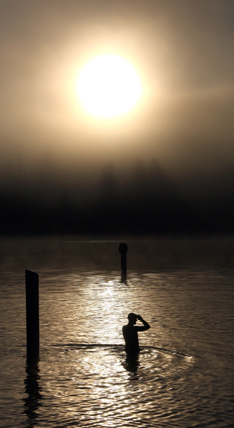It was an early start for participants in the Tri-Turtle Triathlon Sunday morning at Wildcat Lake as a swimmer acclimates to the water temperature before the swimming leg of the competition started Sunday morning. (STEVE ZUGSCHWERDT / SPECIAL TO THE KITSAP SUN)