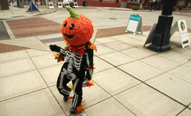 Dressed as Pumpkeleton from My Singing Monsters, Ben Burge, 7, walks along the sidewalk while trick or treating with his siblings Sam and Saria during Downtown Bremerton's 17th Annual Safe Trick of Treat on Thursday, October 31, 2013. (MEEGAN M. REID / KITSAP SUN)