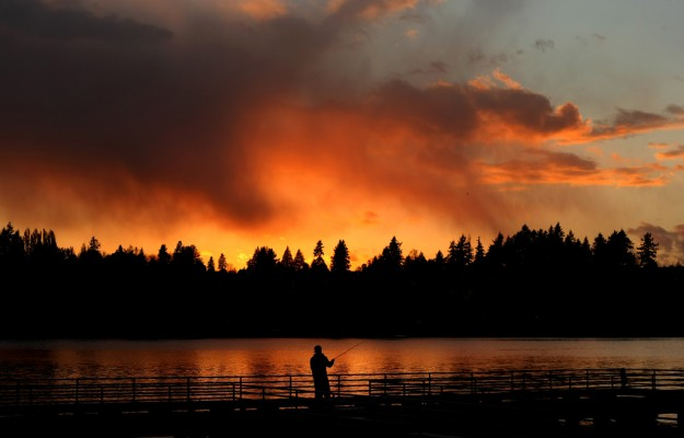 Anthony Gastelum tosses his fishing line into the water at Sunset at the Lions Park Pier on Sunday. (LARRY STEAGALL / KITSAP SUN)