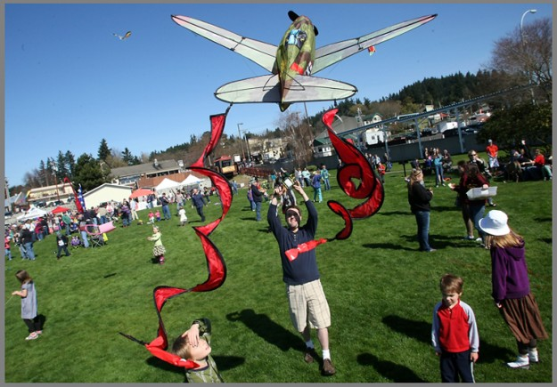 Isaac Anderson, of Kingston, launches his kite into the air as son Cullen, 9, left, looks on at the Kites Over Kingston event on Saturday, March 30, 2013. (MEEGAN M. REID / KITSAP SUN)