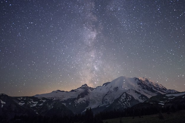 """Celestial Eruption"" Kim Hart This is a gorgeous and very well executed shot of the Milky Way lighting up the sky above Mt. Rainier. I just love the lights of the climbers snaking their way up the snowy face."