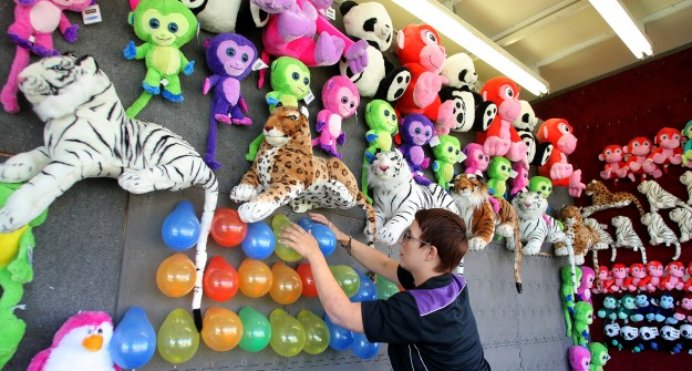 Davis Amusements worker Brenna Coale gets the balloon store game ready for customers at the Kitsap Fair & Stampede. ( LARRY STEAGALL / KITSAP SUN)