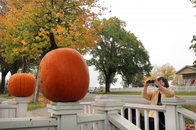 Debbie Short from Whidbey Island takes photos of the pumpkins on the railings of the Estes & Ava Crouse house built in 1903 in Port Gamble. She said Port Gamble is her favorite town in the fall. LARRY STEAGALL / KITSAP SUN