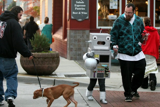 Dressed as a robot, Seth Chadwick, 5, holds his uncle Donald's hand as they cross Pacific Ave. during Downtown Bremerton's 17th Annual Safe Trick of Treat on Thursday, October 31, 2013. (MEEGAN M. REID / KITSAP SUN)