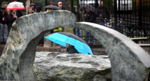 A Puget Sound Naval Shipyard worker is framed by the rock art in the adjacent park on a rainy Wednesday, at the First and Pacific gate. LARRY STEAGALL / KITSAP SUN