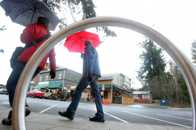 Bainbridge Island ferry commuters are framed by one of the new Bicycle racks on Winslow Way on a wet Thursday morning. LARRY STEAGALL / KITSAP SUN