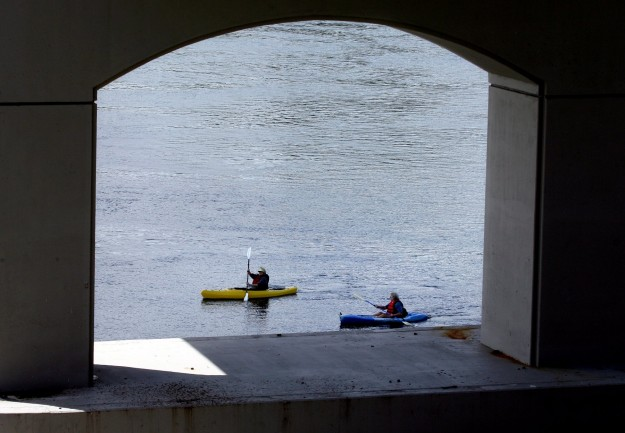 A pair of kayakers are framed by the support pilings to the Manette Bridge on Tuesday. LARRY STEAGALL / KITSAP SUN
