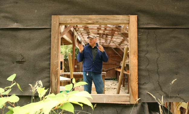 Alan Kasper is framed in a window of the existing rifle range structure as he talks about the improvements that would be made before reopening the rifle range at the Bainbridge Island Sportsmen's Club on Friday, July 12, 2013. (MEEGAN M. REID / KITSAP SUN)
