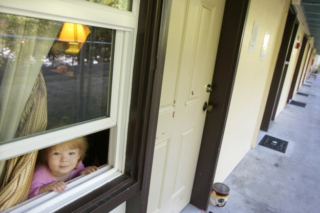 The youngest of a three generation family that lives at the Chieftain Motel in West Bremerton peeks out of her rooms window. LARRY STEAGALL / KITSAP SUN