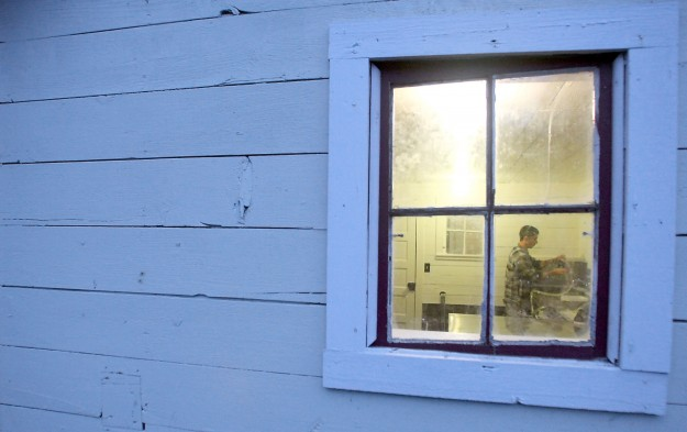 Todd Krause is framed in his barn window as he washes the milking equipment after milking his cows early Wednesday morning. (MEEGAN M. REID/KITSAP SUN)