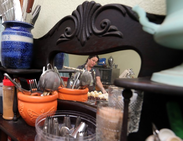 Reflected in the mirror of a vintage hutch that stores her various baking utensils, Trisha O'Meara prepares cupcakes at her newly opened Goody Cottage in Bremerton on Friday, November 21, 2014. (MEEGAN M. REID / KITSAP SUN)