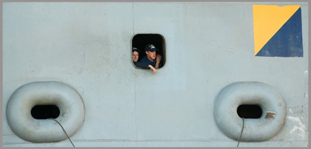 Sailors look out of a porthole in the side of the USS John C. Stennis as it docks at Naval Base Kitsap-Bremerton on Friday, May, 3, 2013. (MEEGAN M. REID / KITSAP SUN)