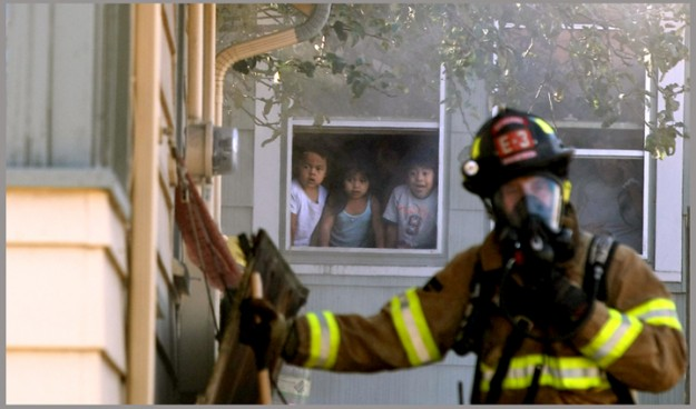 Youngsters watch from a window as Bremerton Firefighter Seth Jackson (left) and a fellow Bremerton crew member help extinguish a fire in the basement of a neighboring house along Warren Avenue in Bremerton on Tuesday, October 1, 2013. Central Kitsap crews also assisted on the call. (MEEGAN M. REID / KITSAP SUN)