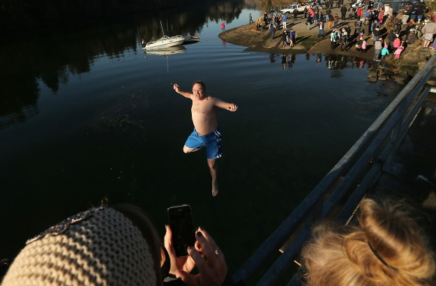 Bystanders on the bridge snap cellphone pictures as Brad Larson, of Gig Harbor, falls toward the water during the annual Olalla Polar Bear Plunge on Monday, January 1, 2015. (MEEGAN M. REID / KITSAP SUN)