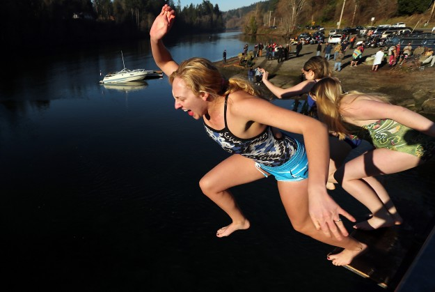 Heidi Edgecombe, of Port Orchard, gives a yell as she makes the jump from the bridge with Savannah Easterday and Nancy Martin at the annual Olalla Polar Bear Plunge on Monday, January 1, 2015. (MEEGAN M. REID / KITSAP SUN)