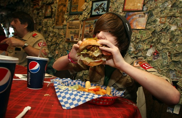 Kyle Deven, 13, takes a bite out of his first Fat Smitty Burger: (two patties, three slices of bread, bacon, lettuce, tomato and sauce) before he and fellow boy scouts helped remove the money adorning the walls of Fat Smitty's restaurant in In Discovery Bay on Saturday, January 28, 2012. Deven was able to finish the giant burger as well as some fries. (MEEGAN M. REID / KITSAP SUN)