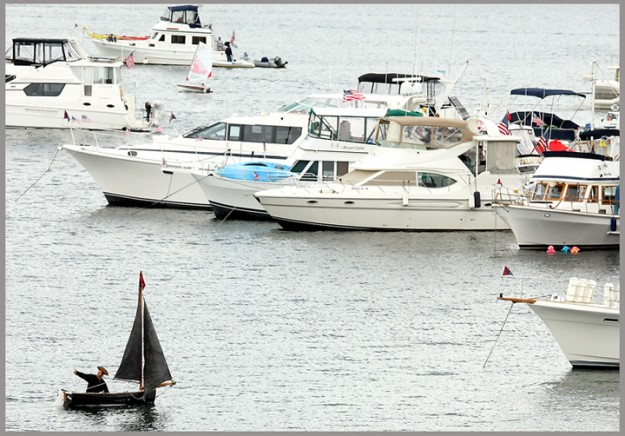 "The captain of a small sailboat named ""Wee Rogue"" gives a thumbs up to a fellow boater as he sails through the plethora of vessels anchored in Poulsbo's Liberty Bay on Monday, July 2, 2012. (MEEGAN M. REID / KITSAP SUN)"