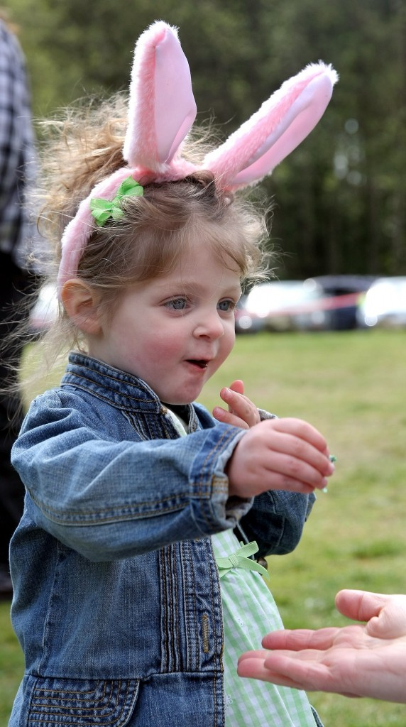 Ellis Osburn, 2, of Bremerton hands her mom Angie her candy wrapper after sampling some that she got at the South Kitsap Regional Park on Saturday for the Fathoms O' Fun Easter Egg Hunt. (LARRY STEAGALL / KITSAP SUN)