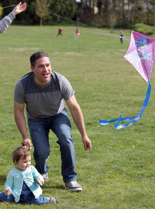Dan Kieta of Bremerton smiles as he watches his granddaughter Eveyln Bodnar, 1, kite go up as she holds the string Monday at Blueberry park in Bremerton. (LARRY STEAGALL / KITSAP SUN)