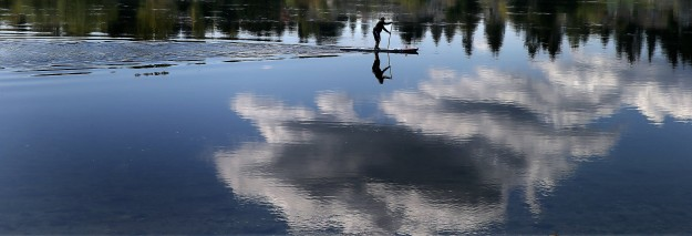 James Morton of Bremerton takes advantage of the still water and warm day to standup paddle near the Lions Park boat ramp on Thursday. (LARRY STEAGALL / KITSAP SUN)