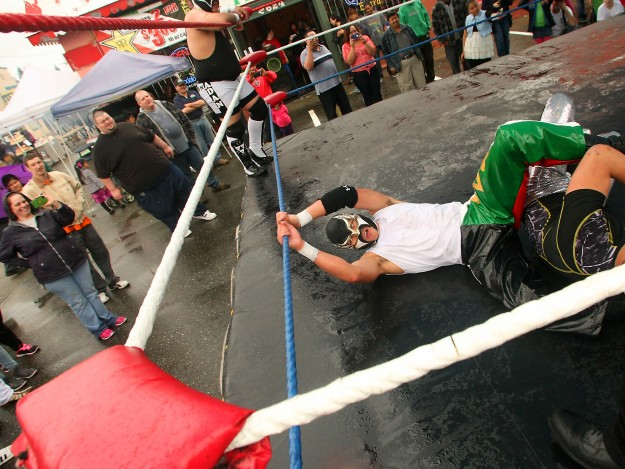 Luchador El Sonico holds onto the rope of the ring as he puts a leg hold on his opponent Cromo at the Cinco de Mayo celebration in Bremerton on Saturday, May 3, 2014. (MEEGAN M. REID /KITSAP SUN)