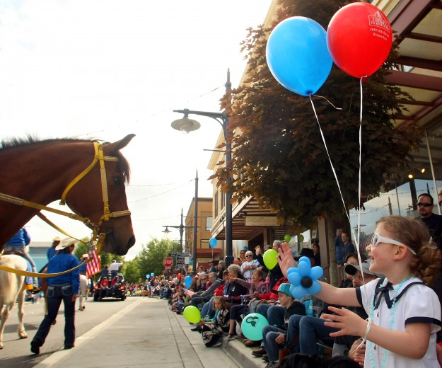 Isabelle Roe, 3, waves to a horse as she watches the annual Armed Forces Day Parade in Bremerton, Washington on Saturday, May 17, 2014. (AP Photo/ Kitsap Sun, Meegan M. Reid)