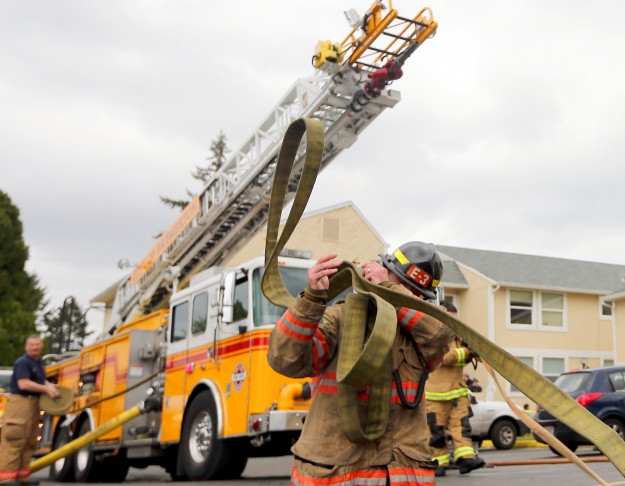Bremerton Firefighter Aaron Stanio gathers hose on his shoulder as he and fellow firefighters gather their gear after extinguishing a fire at an apartment complex on 12th. Street in Bremerton on Thursday April 23, 2015. (MEEGAN M. REID / KITSAP SUN)