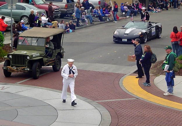 Armed Forces Day Parade by Greg Patterson I really like this shot of U.S. Navy World War II veteran Burke Waldron as he turns onto 4th. Street during Bremerton's Armed Forces Day parade. I am a fan of the high angle utilized by Greg and his composition that not only showcases basically everything you want to capture in a parade scene (participants, onlookers, etc.) but also captures the leading line of the road from the upper right off the frame and guides the viewers eyes through every part of the image down to the lower right corner.