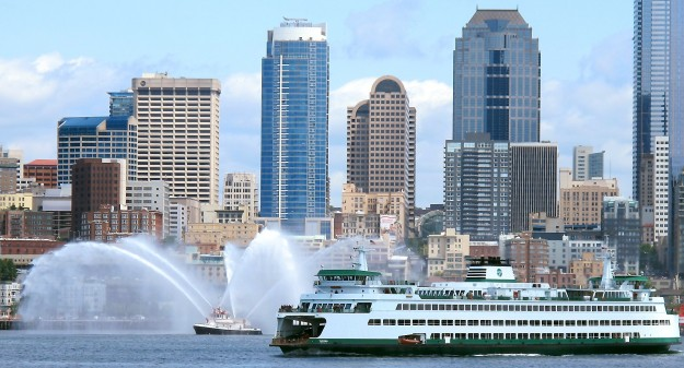 The ferry Tacoma sails from Seattle to Bainbridge Island past a Seattle Fire Department boat conduction pump tests along the waterfront in this June 2012 file photo. (MEEGAN M. REID/KITSAP SUN)