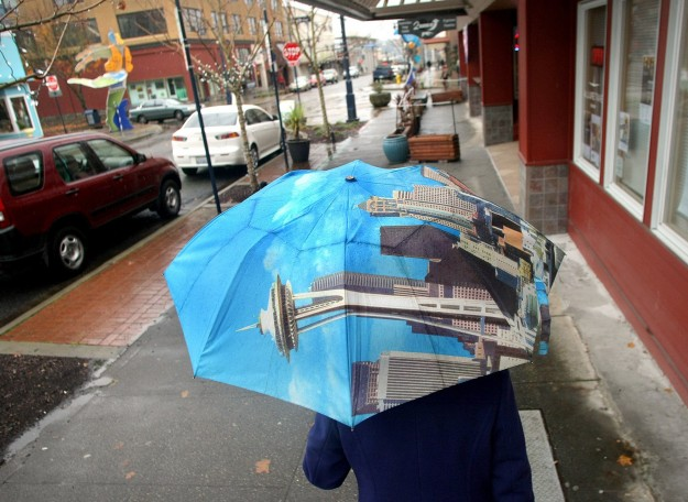 Edith Clark of Bremerton covers up with her Seattle and Space Needle umbrella as she walks on Pacific Ave. in downtown Bremerton on a wet and windy Wednesday. LARRY STEAGALL / KITSAP SUN