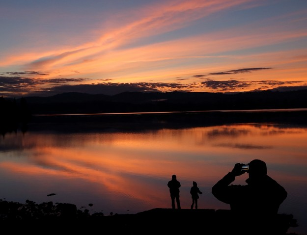 Photographs are snapped as the sky lights up over the Tracyton Boat Launch at sunset on Friday, January 9, 2015. (MEEGAN M. REID / KITSAP SUN)