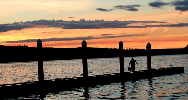 As the setting sun paints the sky over Salsbury Point Park, Alan Rogers, of Poulsbo, carries a bucket down the dock after a day of crabbing on Sunday, June 21, 2015. (MEEGAN M. REID / KITSAP SUN)