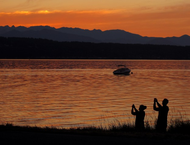 Photographs are snapped as the sun begins to set at the Tracyton boat launch on Thursday, July 2, 2015. (MEEGAN M. REID / KITSAP SUN)