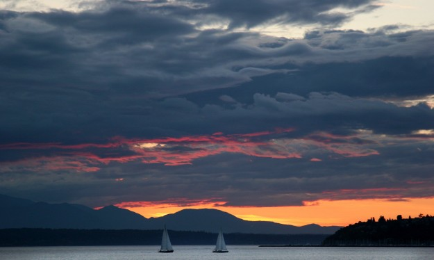 A pair of sailboats head towards Seattle on Elliott Bay, with Bainbridge Island in the background at sunset on Monday. LARRY STEAGALL / KITSAP SUN
