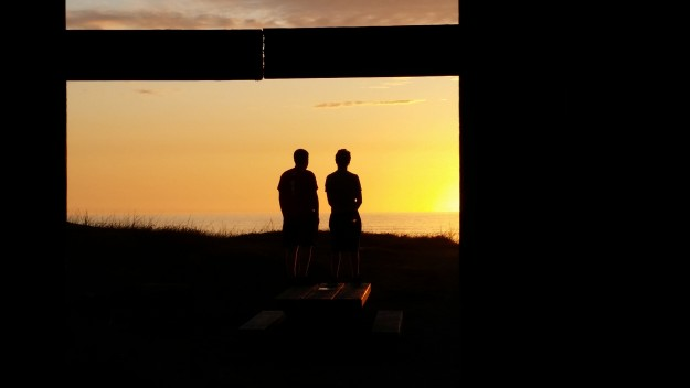 By John Lax 07/12/2015 Northern California beach (west of Orick). Through a covered picnic patio toward open ocean sunset.
