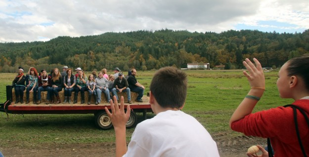 Hayride passengers wave to a passing hay wagon going in the opposite direction as they leave the pumpkin patch at Hunter Farms in Union on Sunday, October 19, 2014. (MEEGAN M. REID / KITSAP SUN)