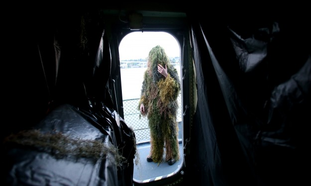 Alexander Nemechik adjusts his ghillie suit as he prepares to take his position aboard the USS Turner Joy for the Haunted Ship Tormented Tales: Island of Dolls tours on Tuesday, October 28, 2014. (MEEGAN M. REID / KITSAP SUN)