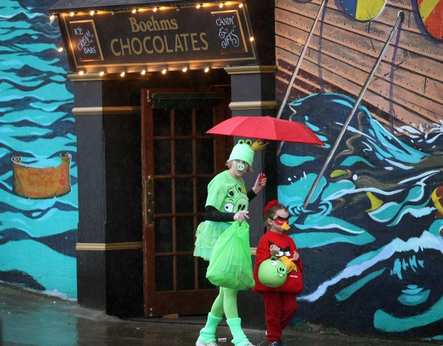 Kellie Bickel hold an umbrella to keep her and son Shay, 5, dry as they trick or treat as character from Angry Birds in downtown Poulsbo on Thursday, October 31, 2014. (MEEGAN M. REID / KITSAP SUN)