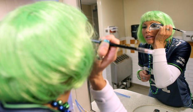 Heather Kennedy, of Bremerton, touches up her Seahawk makeup in the bathroom of the ferry as she heads to the game on Sunday. (MEEGAN M. REID/KITSAP SUN)