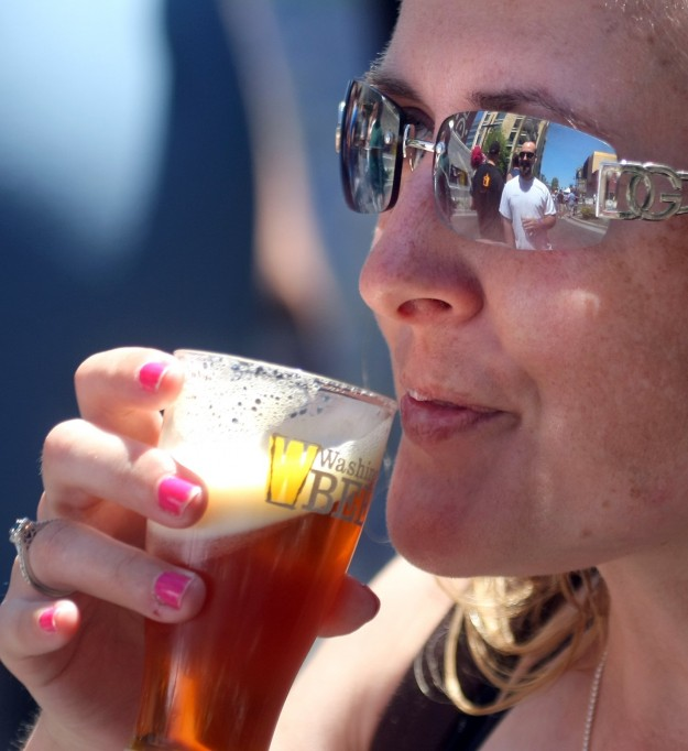 Juliet Roske of Bremerton has her husband Rob Roske reflected in her glasses at the Bremerton BrewFest on Saturday. LARRY STEAGALL / KITSAP SUN