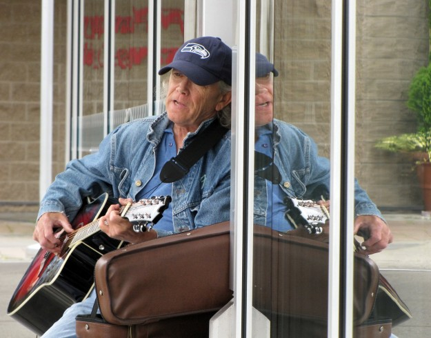 Gary Mason of Bremerton plays his guitar outside of Starbucks and is reflected in the windows in downtown Bremerton near the Bremerton Transportation Center on Wednesday. He is using his new guitar. LARRY STEAGALL / KITSAP SUN