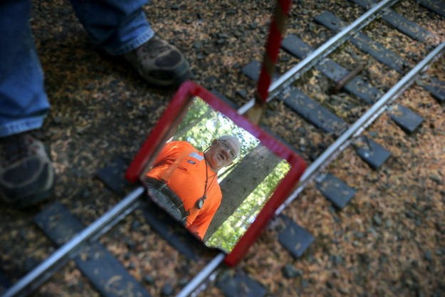 Nelson Lanchester of Port Orchard of the Kitsap Live Steamers in reflected in the mirror which is used to see if the track is straight. Members of the club were fixing the track Friday morning which was damaged by vandals. LARRY STEAGALL / KITSAP SUN