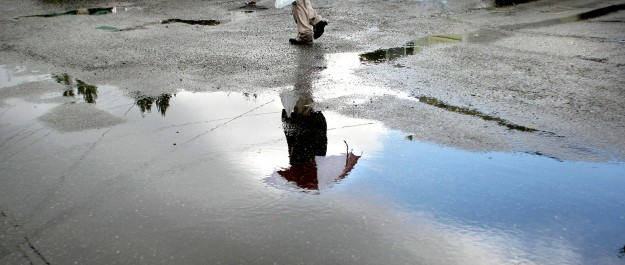 An umbrella is reflected in a rain puddle at Perry and Sheridan Rds. in Bremerton on Monday. LARRY STEAGALL / KITSAP SUN