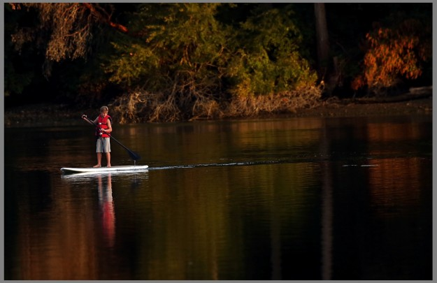 Kainoa Bonsell, 10, paddle boards through the reflective waters of Dogfish Bay in Keyport, Wash. on Monday August 10, 2015. (MEEGAN M. REID / KITSAP SUN)