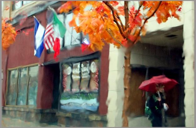 The view through a rain soaked windshield causes a painterly effect as a pedestrian with an umbrella walks along Pacific Avenue in Bremerton, Wash. on Monday, November 19, 2012. (AP Photo/ Kitsap Sun, Meegan M. Reid)
