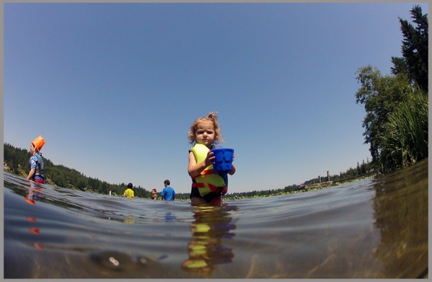Audina Michaud, 2, carries a bucket of water back to the shore for sand castle construction at Kitsap Lake Park in Bremerton on Monday, July 1, 2013. (MEEGAN M. REID / KITSAP SUN)