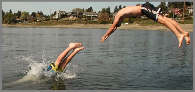 Nathan Thompson, 16, and Thor Breitbarth, 16, dive into the water from the dock at Oyster Plant Park in Poulsbo, Wash. on a sunny and warm Tuesday, April 29, 2014. (MEEGAN M. REID /KITSAP SUN)