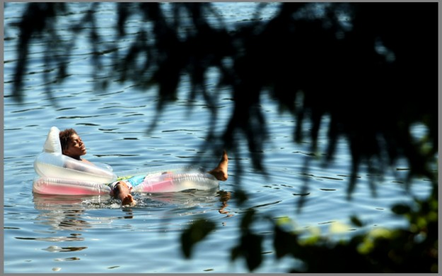 Kaseem Bell, 11, floats in Wildcat Lake on a sunny and warm Monday, July 28, 2014. (MEEGAN M. REID / KITSAP SUN)